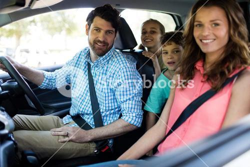 Happy family sitting in car
