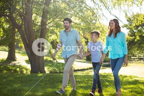 Happy family with hand in hand walking in park