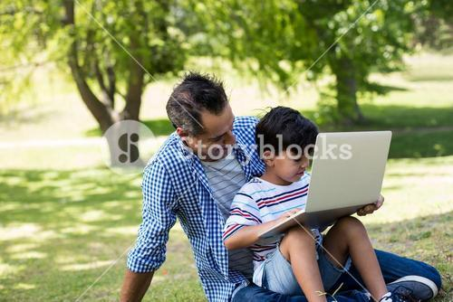 Boy sitting on his fathers lap and using laptop in park