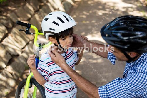 Father assisting son in wearing bicycle helmet in park