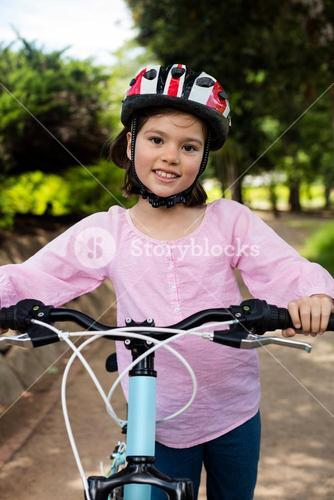 Portrait of smiling girl standing with bicycle in park