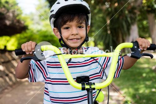 Portrait of smiling boy standing with bicycle in park