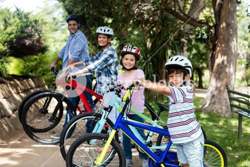 Portrait of parents and children standing with bicycle in park