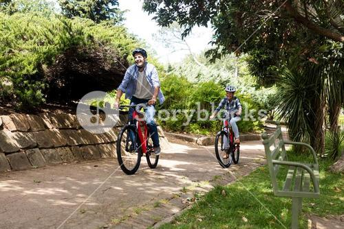 Happy couple cycling in park