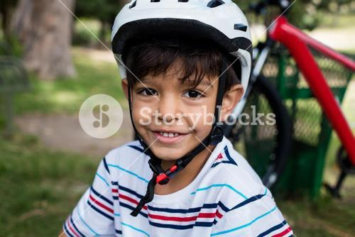 Portrait of smiling boy wearing bicycle helmet in park