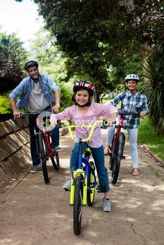 Portrait of happy parents and daughter standing with bicycle in park