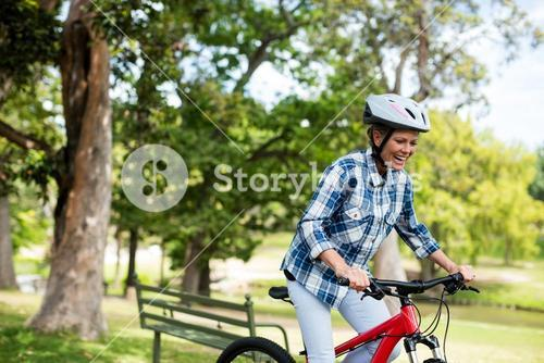Happy woman cycling in park