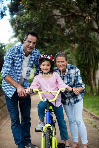 Portrait of happy parents assisting daughter to ride bicycle in park