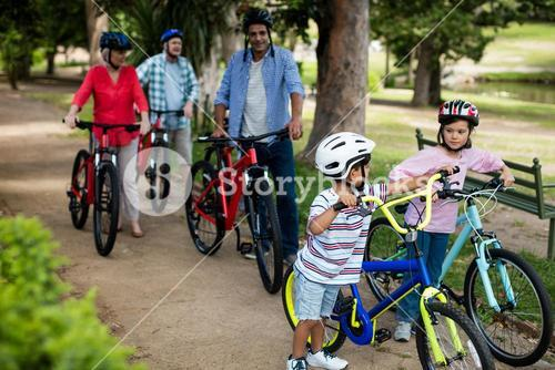 Multi-generation family walking with bicycle in park