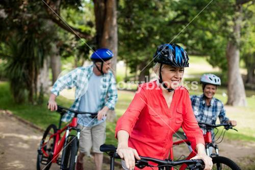 Parents and daughter walking with bicycle in park