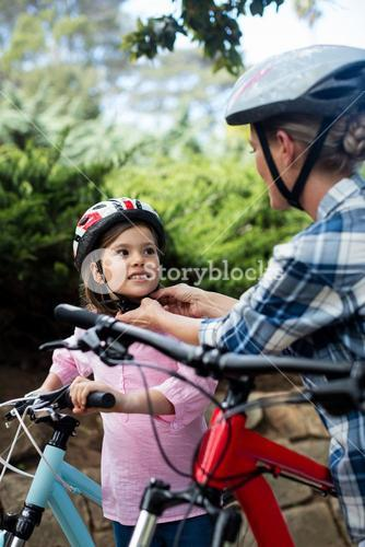 Mother assisting daughter in wearing bicycle helmet in park