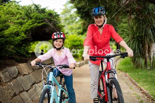Grandmother and granddaughter cycling in park