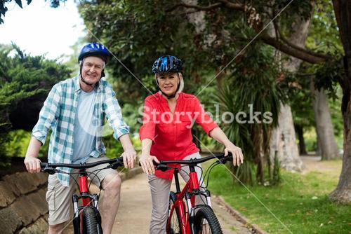 Portrait of senior couple standing with bicycle in park