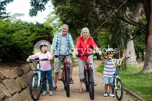 Portrait of multi-generation family standing with bicycle in park