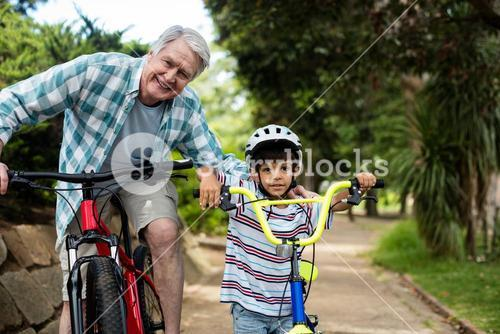 Portrait of grandfather and grandson standing with bicycle in park