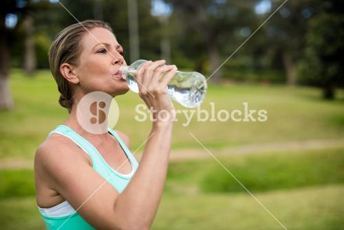Female athlete drinking water in park