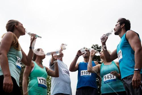 Athletes drinking water in park