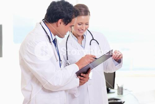 Assistant doctors reading off clip board