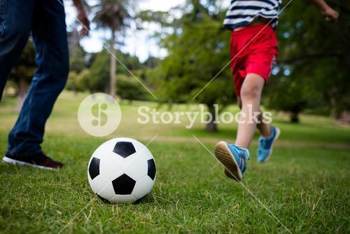 Low section of father and son playing football