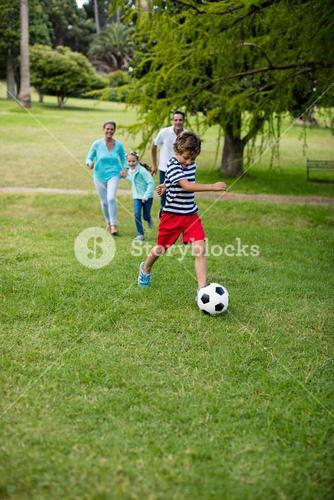 Happy family playing football in park