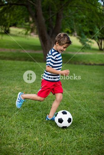 Boy playing football in park