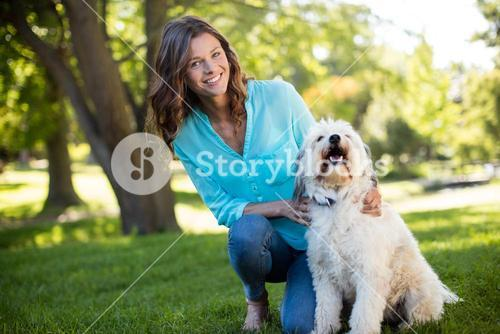 Portrait of woman with dog in park