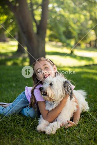 Portrait of girl with dog in park