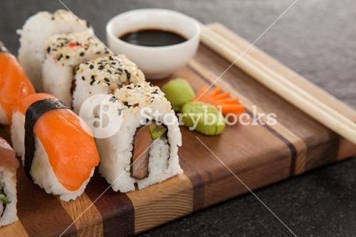 Assorted sushi set served with chopsticks and soy sauce on wooden board
