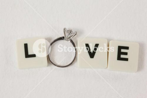 Diamond ring between white blocks displaying love message