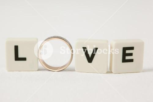 Ring between white blocks displaying love message