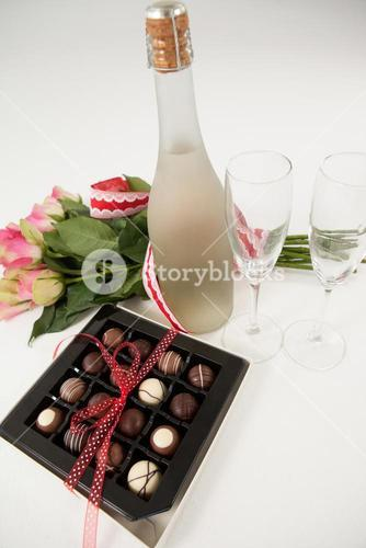 Bunch of roses, champagne bottle, wine glasses and assorted chocolate box