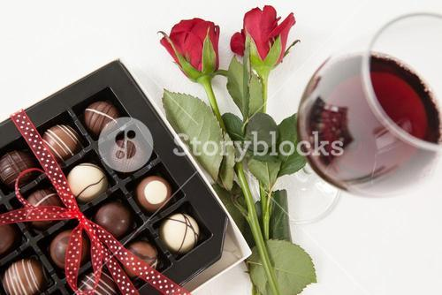 Bunch of roses, champagne bottle, wine glass and assorted chocolate box
