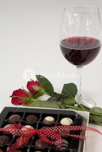 Bunch of roses, wine glass and assorted chocolate box