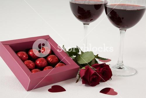 Bunch of roses, wine glasses and assorted chocolate box