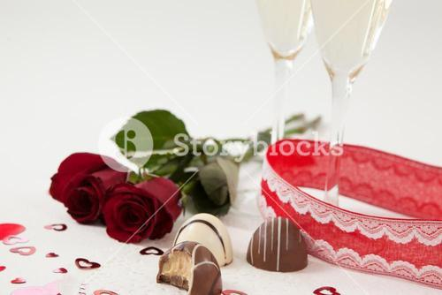 Bunch of roses, champagne glass and assorted chocolate