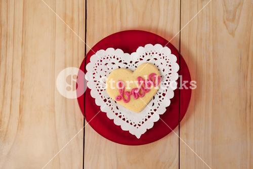 Heart shaped cookie iced with pink cream in text babe