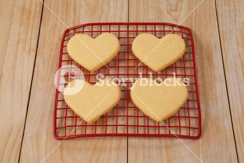 Four heart shaped cookie kept on cooling tray