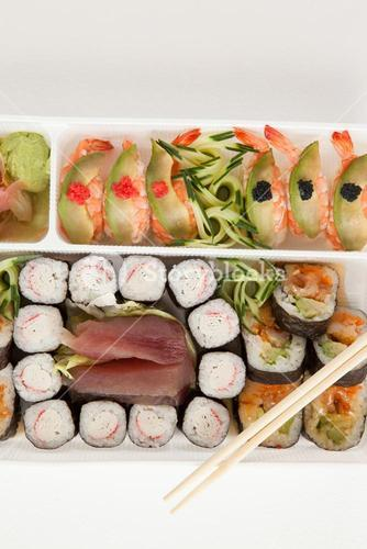 Assorted sushi set served with chopsticks in white box against white background