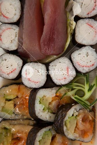 Assorted sushi set served in white box against white background