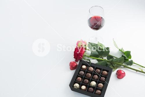 Chocolate box, roses and red wine glass on white background