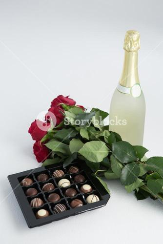 Chocolate box, roses and champagne bottle on white background