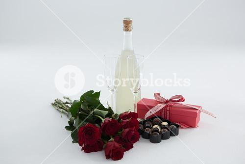 Gift, chocolate box, roses and champagne bottle on white background
