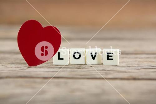 Red heart next to white blocks displaying love message