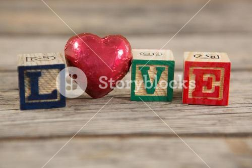 Red heart between blocks displaying love message