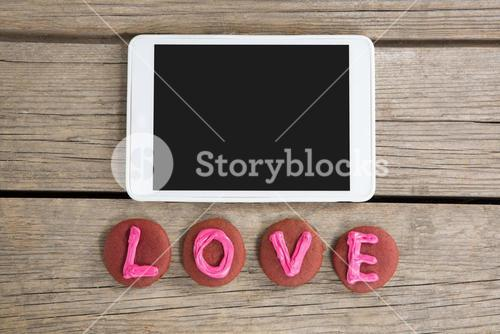 Digital tablet with cookies displaying love message on wooden surface