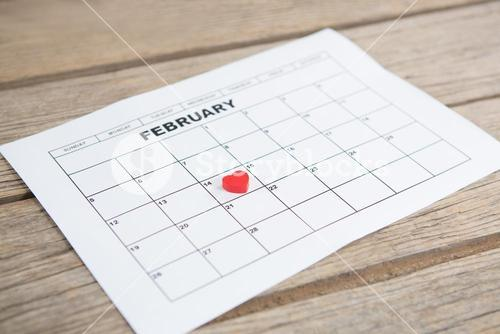 Red heart shape placed on 14th february date of the calendar