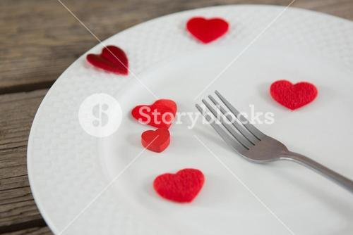 White plate with red hearts and fork