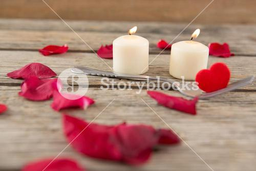Burning candles surrounded with aromatic rose petals