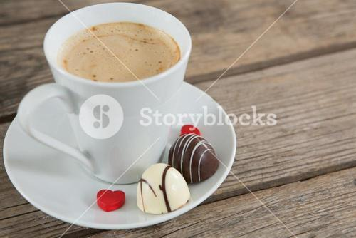 Cup of coffee with chocolate and confectionery