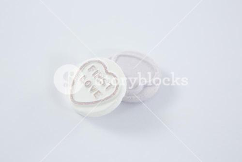 Heart shape confectionery with text first love
